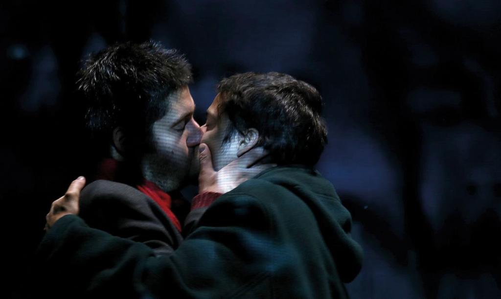 Deux homme brun en sweatshirt s'embrasse passionnément.