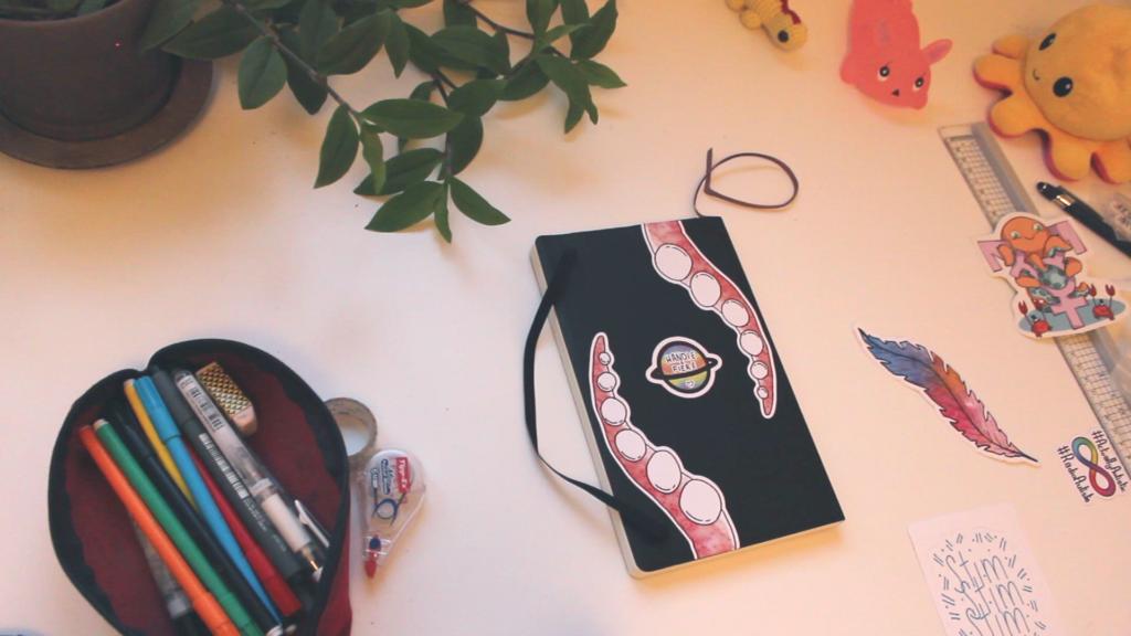 """Carnet noir avec au dos deux stickers représentants des tentacule de poulpe et au centre une planète multi colore indiquant """"handi·e et fier·e"""""""
